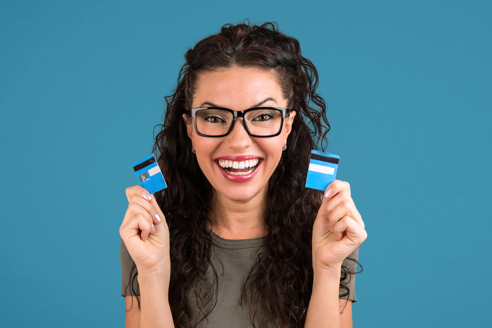 Happy debt free woman in glasses holding a credit card cut in two pieces