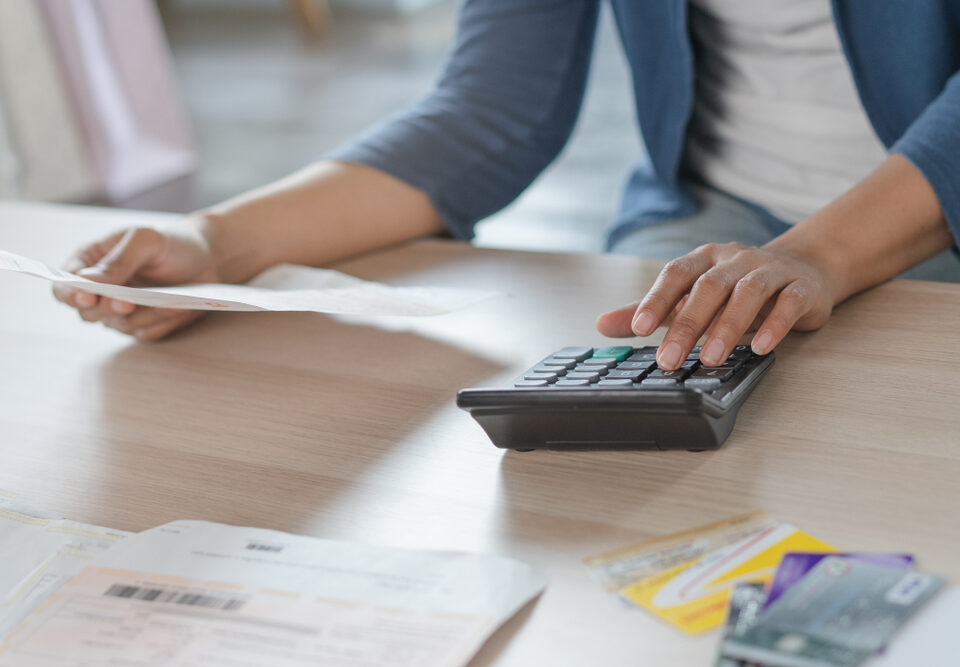 Close up businessman hand calculating monthly expense and credit card debt.