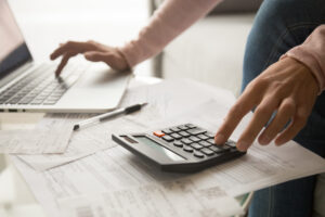 young woman calculating monthly expenses, managing budget - Prudent Financial Solutions