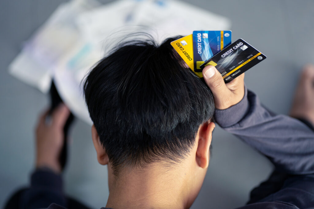 Sad confused and stressed young man holding credit cards - Prudent Financial Solutions