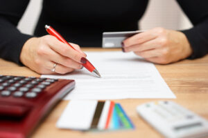 woman writing and checking credit card information - Prudent Financial Solutions