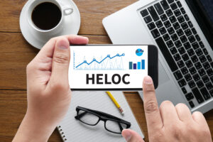 HELOC (Home Equity Line of Credit) message on hand holding to touch a phone - Prudent Financial Solutions