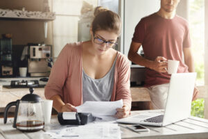 female in glasses holding piece of paper and making necessary calculations - Prudent Financial Solutions