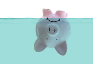 frowning pink piggy bank floating upside down under water, on white - Prudent Financial Solutions