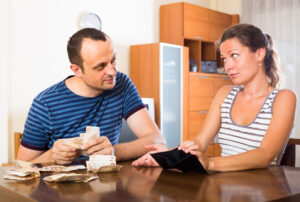 young couple talking about their spending habit at the kitchen table