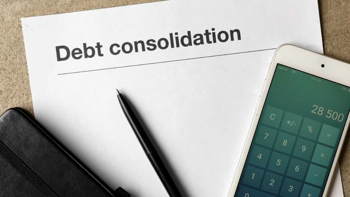 pen and calculator app on top of debt consolidation form